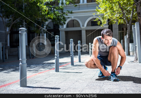 Handsome athlete tying his shoe laces  stock photo, Handsome athlete tying his shoe laces on a sunny day by Wavebreak Media