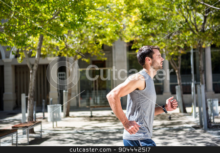 Handsome athlete running in the street stock photo, Handsome athlete running in the street on a sunny day by Wavebreak Media