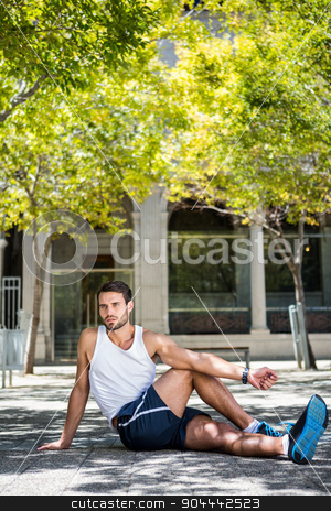Handsome athlete stretching his leg on the ground stock photo, Handsome athlete stretching his leg on the ground in the city by Wavebreak Media