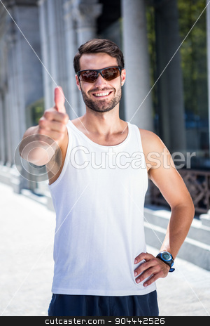 Smiling handsome athlete doing thumbs up stock photo, Portrait of smiling handsome athlete doing thumbs up in the city by Wavebreak Media