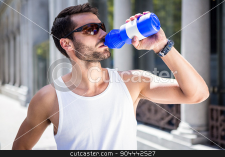 Handsome athlete with sunglasses drinking out of bottle stock photo, Handsome athlete with sunglasses drinking out of bottle in the city by Wavebreak Media