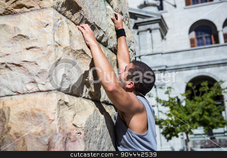 Extreme athlete gripping to wall stock photo, Extreme athlete gripping to wall in the city by Wavebreak Media