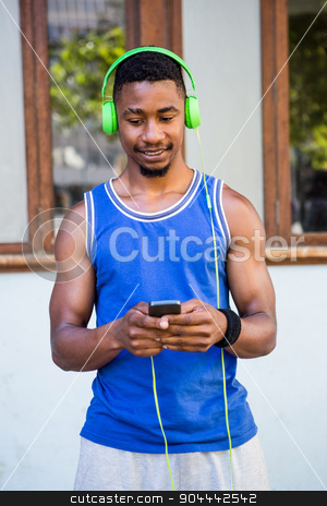 An handsome athlete listening to music stock photo, An handsome athlete listening to music on a sunny day by Wavebreak Media