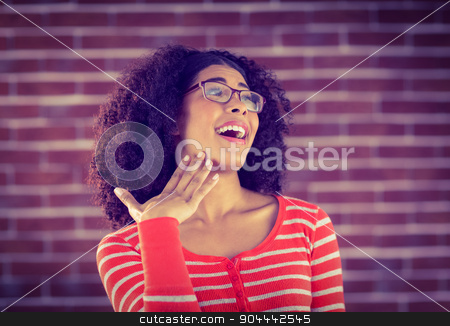 Surprised attractive young woman stock photo, Surprised attractive young woman against red brick background by Wavebreak Media