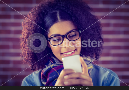 Smiling attractive hipster texting stock photo, Smiling attractive hipster texting against red brick background by Wavebreak Media