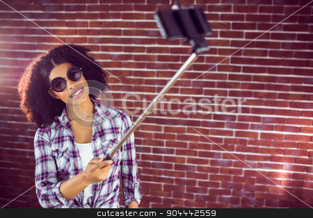 Attractive hipster taking selfies with selfiestick stock photo, Attractive hipster taking selfies with selfiestick against red brick background by Wavebreak Media