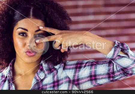 Attractive young woman showing peace sign stock photo, Portrait of attractive young woman showing peace sign against red brick background by Wavebreak Media