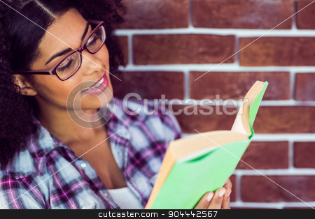 Attractive hipster reading book stock photo, Attractive hipster reading book against red brick background by Wavebreak Media