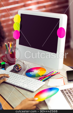 Female graphic designer working at desk stock photo, Female graphic designer working at desk against red brick background by Wavebreak Media