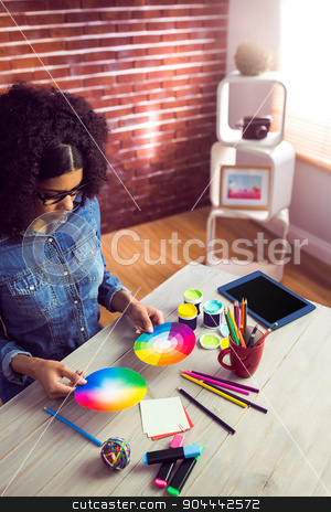 Casual businesswoman holding a color wheel  stock photo, Casual businesswoman holding a color wheel in her office by Wavebreak Media