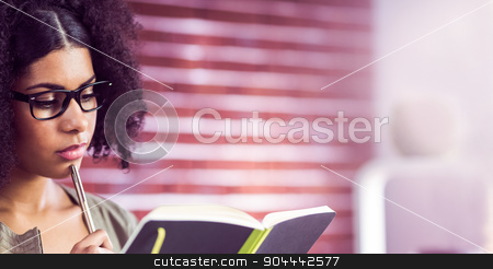 Casual businesswoman looking in her diary stock photo, Casual businesswoman looking in her diary in her office by Wavebreak Media