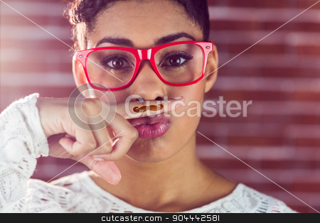 Portrait of a happy hipster wearing a fake mustache stock photo, Portrait of a happy hipster wearing a fake mustache on her finger by Wavebreak Media