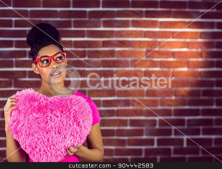 Portrait black hair model holding a pink heart shaped pillow stock photo, Portrait black hair model holding a pink heart shaped pillow on a red brick wall by Wavebreak Media