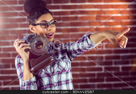 Young hipster with camera pointing stock photo, Young hipster with camera pointing at something against a brick wall  by Wavebreak Media