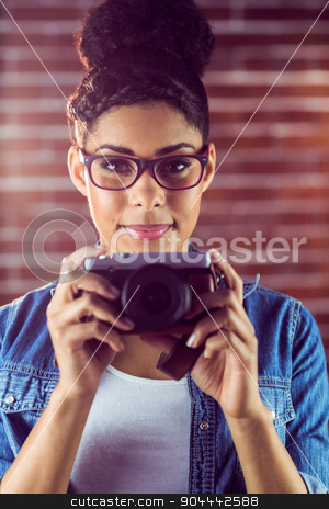 Portrait of a young hipster taking a picture  stock photo, Portrait of a young hipster taking a picture against a brick wall by Wavebreak Media