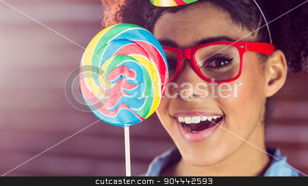 Young woman holding a lollipop against her face  stock photo, Young woman holding a lollipop against her face on a re brick wall by Wavebreak Media