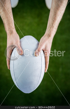 Rugby player catching a rugby ball stock photo, Upward view of a rugby player catching a rugby ball by Wavebreak Media