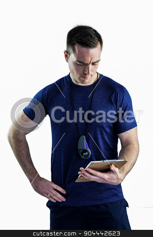 Attentive trainer looking at his clipboard stock photo, Attentive trainer looking at his clipboard on a white background by Wavebreak Media