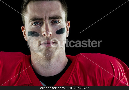 Smiling american football player looking at camera stock photo, Portrait of a smiling american football player on a shadow background by Wavebreak Media