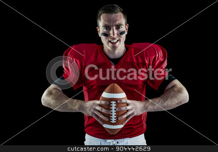 American football player holding a ball stock photo, Portrait of a determined american football player holding a ball by Wavebreak Media