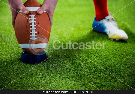 American football player preparing for a drop kick stock photo, American football player preparing for a drop kick on american football field by Wavebreak Media