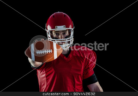 Portrait of american football player showing football to camera stock photo, Portrait of american football player showing football to camera against black background by Wavebreak Media