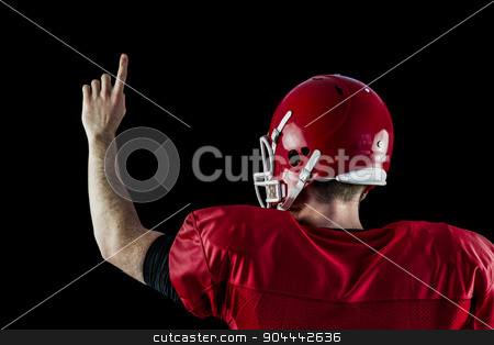 Rear view of american football player triumphing  stock photo, Rear view of american football player triumphing against black background by Wavebreak Media
