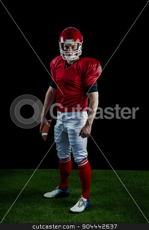 Portrait of american football player holding football stock photo, Portrait of american football player holding football against black background by Wavebreak Media
