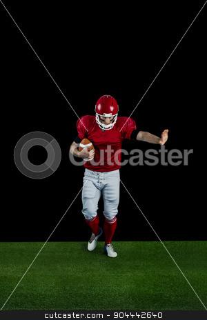 American football player wrestling through and protecting footba stock photo, American football player wrestling through and protecting football on american football field by Wavebreak Media