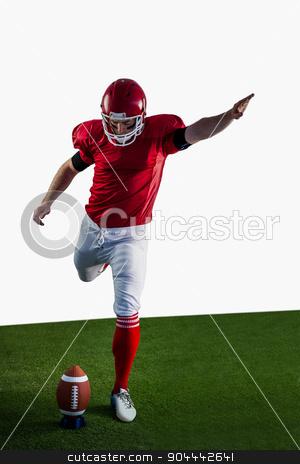American football player kicking football stock photo, American football player kicking football on american football field by Wavebreak Media