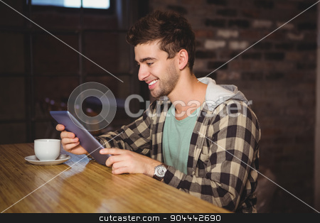 Smiling hipster sitting and using tablet computer stock photo, Smiling hipster sitting and using tablet computer at coffee shop by Wavebreak Media