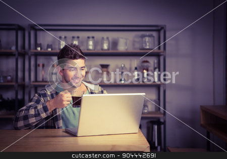 Smiling hipster drinking coffee and using laptop stock photo, Smiling hipster drinking coffee and using laptop at coffee shop by Wavebreak Media