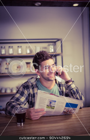 Smiling hipster phoning and holding newspaper stock photo, Smiling hipster phoning and holding newspaper at coffee shop by Wavebreak Media