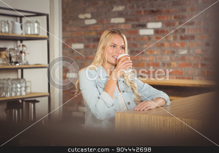 Smiling blonde drinking out of take-away cup stock photo, Smiling blonde drinking out of take-away cup at coffee shop by Wavebreak Media