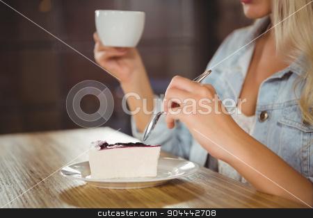 Woman enjoying cake and coffee stock photo, Woman enjoying cake and coffee at coffee shop by Wavebreak Media