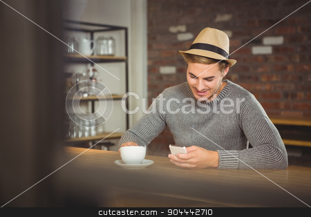 Handsome hipster having coffee and using smartphone stock photo, Handsome hipster having coffee and using smartphone at coffee shop by Wavebreak Media