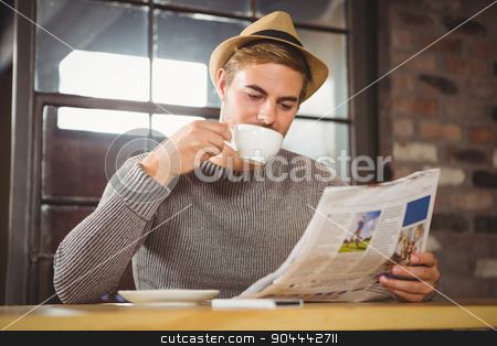 Handsome hipster drinking coffee and reading newspaper stock photo, Handsome hipster drinking coffee and reading newspaper at coffee shop by Wavebreak Media