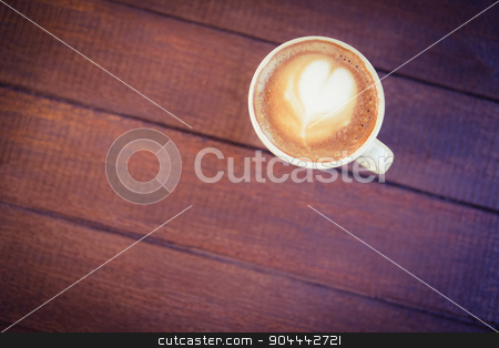 Cup of cappuccino with coffee art on wooden table stock photo, Cup of cappuccino with coffee art on wooden table at coffee shop by Wavebreak Media