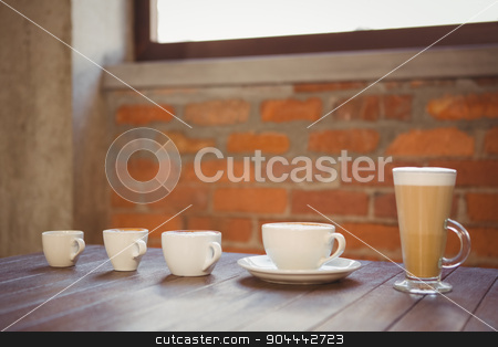 Several hot beverages in a row on wooden table stock photo, Several hot beverages in a row on wooden table at coffee shop by Wavebreak Media