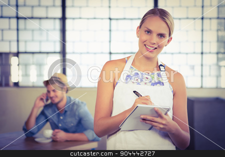 Portrait of a beautiful waitress taking an order stock photo, Portrait of a beautiful waitress taking an order in a cafe by Wavebreak Media
