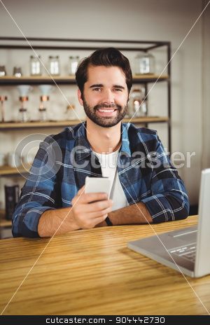 Young student enjoying a coffee and using his smartphone stock photo, Young student enjoying a coffee and using his smartphone in a cafe by Wavebreak Media