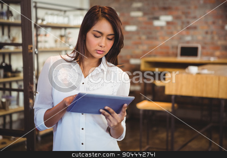 Smiling young businesswoman holding a tablet stock photo, Smiling young businesswoman holding a tablet in her office by Wavebreak Media