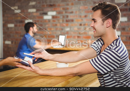 Paying for a croissant and a coffee with his smartphone stock photo, Paying for a croissant and a coffee with his smartphone at a cafe by Wavebreak Media