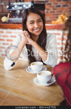 Female friends having coffee stock photo, Two smiling friends having coffee at coffee shop by Wavebreak Media