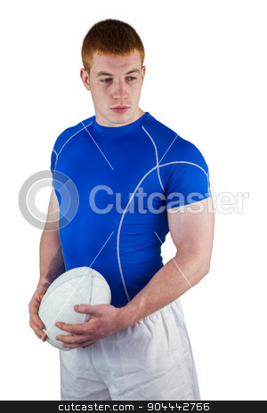Serious rugby player holding rugby ball stock photo, Portrait of a rugby player holding rugby ball and looking down by Wavebreak Media