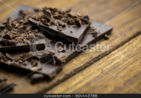 Pieces of chocolate on a wooden table stock photo, Close up view of pieces of chocolate on a wooden table by Wavebreak Media
