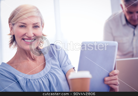 Smiling businesswoman looking at the camera stock photo, Portrait of a businesswoman working on tablet at the office by Wavebreak Media
