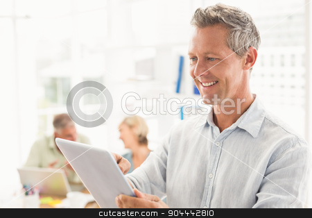 Smiling businessman scrolling on a tablet stock photo, Smiling businessman scrolling on a tablet at the office by Wavebreak Media
