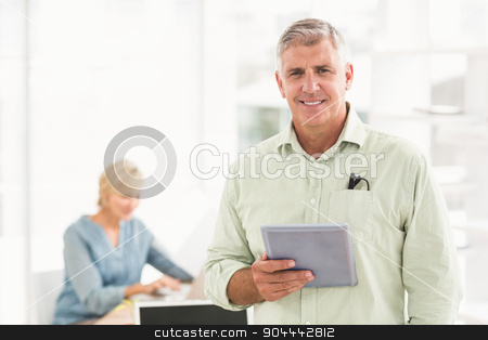 Standing smiling businessman looking at the camera stock photo, Portrait of a standing businessman holding a tablet at the office by Wavebreak Media