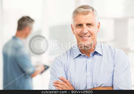 Smiling businessman with arms folded stock photo, Portrait of a smiling businessman with arms folded at the office by Wavebreak Media